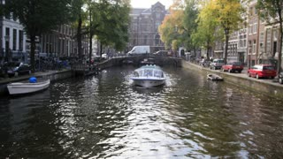 Tour boat sails in Amsterdam canal, Holland, Netherlands