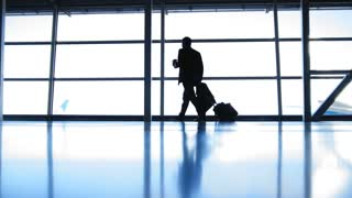Travellers - aircraft commander with coffee to go going in airport in front of window, silhouette