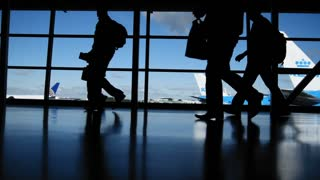 Travellers in airport in front of window, silhouette