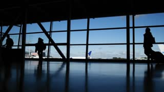 Travellers with suitcases and baggage in airport walking to departures in front of window, silhouette