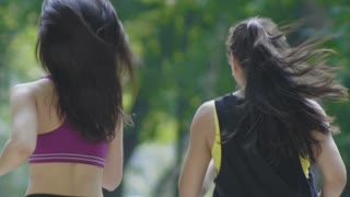 Two attractive Fitness athletic young women with curly hair dressed in sport clothes running in the park at summer morning, rear view close up