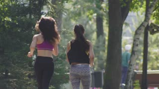 Two attractive Fitness athletic young women with curly hair dressed in sport clothes running in the park at summer morning, rear view