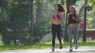 Two attractive Fitness athletic young women with curly hair dressed in sport clothes running in the park at summer morning, slow motion
