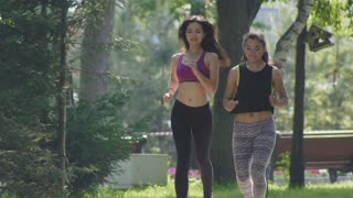 Two attractive Fitness athletic young women with curly hair running in the park at summer morning