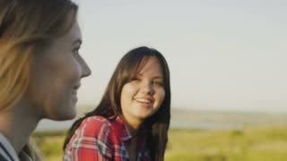 Two attractive girls friends young female standing on high hill and conversations at summer evening, close up