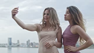 Two Attractive young women in party dresses on high hill get a selfie by smartphone, close up