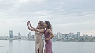 Two Attractive young women in party dresses on high hill get a selfie by smartphone, wide shot