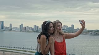 Two young beautiful girls having fun and making selfie on high hill over the city