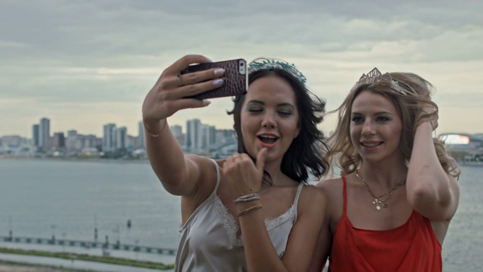 Two young beautiful girls making selfie on high hill over the city Stock Video Footage - Storyblocks