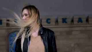 Сute girl with long blonde hair in leather jacket with straightens hair standing in metro against the background of a train coming