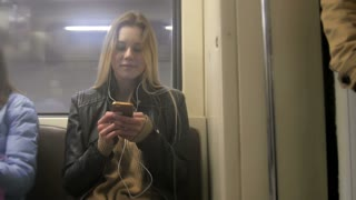 Сute happy girl with long blonde hair in leather jacket with straightens hair use gadget in metro