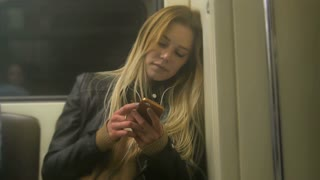 Сute tired girl with long blonde hair in leather jacket with straightens hair use gadget in metro