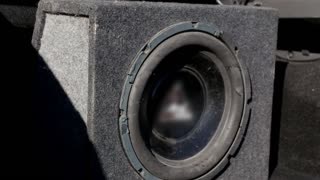 A black vibrating old ragged working subwoofer in car