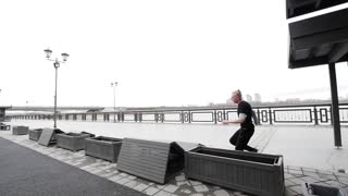 A free run - a tracer blonde man jumps a flip at park, parkour