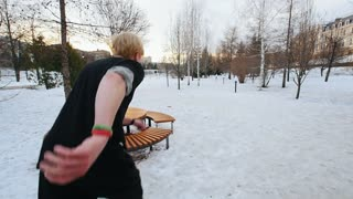 A free-runner tracer jumps flip in winter city park, slow-motion