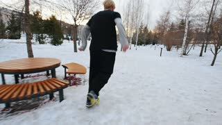 A free-runner tracer jumps in winter city park, slow-motion