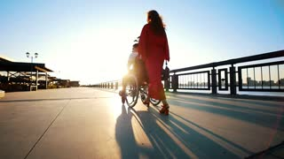 A Girl With Red Hair In Orange Dress Rolls A Disabled Guy In A Wheelchair On The Waterfront In The Sunset