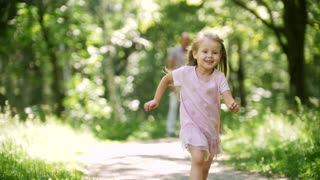 A little girl runs toward the camera in park, slow-motion