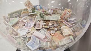 A lot of different bills - money of different countries in big glass jar