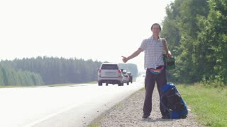 A man in a plaid shirt, a blue hat, with an accordion on his shoulder standing by the road and honking passing cars, lying next to the backpack.