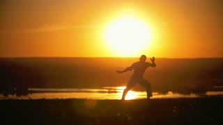 A man performs acrobatic stunts, somersault, orange sunset, slow-motion