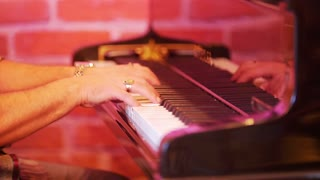 A man plays the piano keys. In the frame of men's hands. On the fingers gold rings.