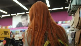 A red hair woman walking in shoes store