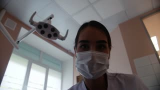 A woman dentist in a mask directs the light of the lamp to the camera. The dentist's office.