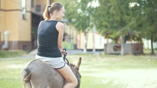 A woman riding a donkey in the stables