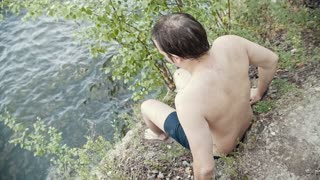 A young man jumps in the river, brave action - slow motion