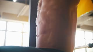 Abs of performing vertical knee rise exercise on the crossbar bodybuilder. Close up shot