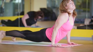 Adult mature women stretching out in fitness room - yoga training