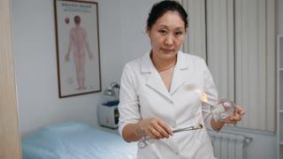 Alternative Asian Tibetan medicine, asian woman doctor prepares a glass jar
