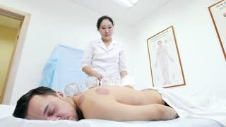 Alternative Asian Tibetan medicine, treatment using glass jars, doctor remove jars