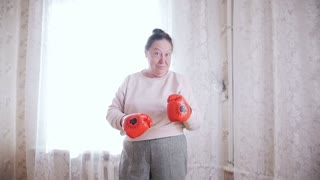 An old senior woman boxing in slow motion