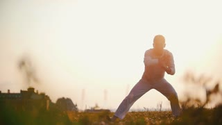 Athletic male in a white tracksuit dancing capoeira on the grass, the glare of the sun, sunset