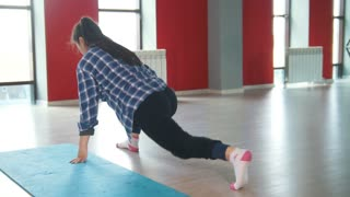 Attractive female brunette stretching in fitness room