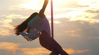 Attractive female pole-dancer rotating on the pole at sunset