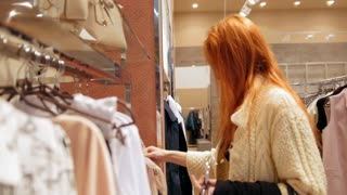 Attractive girl in a fashion dress store chose a clothe - shopping concept