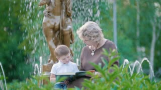 Attractive grandmother and little boy reading a book near the fountain in summer park