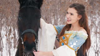 Attractive long haired brunette in a dress and her horse in winter, kissing and smiling