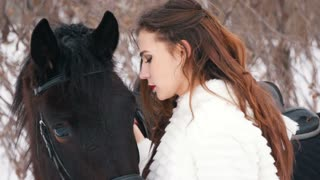 Attractive long haired brunette in a dress and her horse in winter