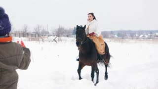 Attractive long haired brunette in a dress galloping on a horse