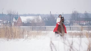 Attractive young brunette in a red dress galloping fast on a horse through the snow-covered field in the winter