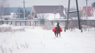 Attractive young brunette in a red dress galloping fast on a horse through the snow in the winter