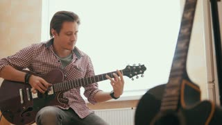 Attractive young man musician composes music on the guitar and plays, other musical instrument in the foreground