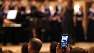 Audience in concert hall - people shooting performance on smartphone, music opera