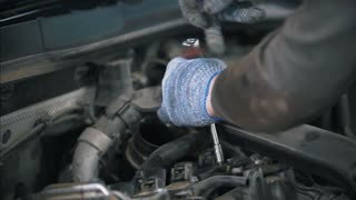 Auto mechanic in gloves wrapping wrench in auto parts