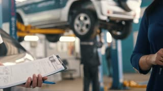 Auto service - woman gives the keys of car for mechanic