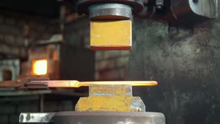 Automatic hammering - blacksmith forging red hot iron on anvil, extreme close-up